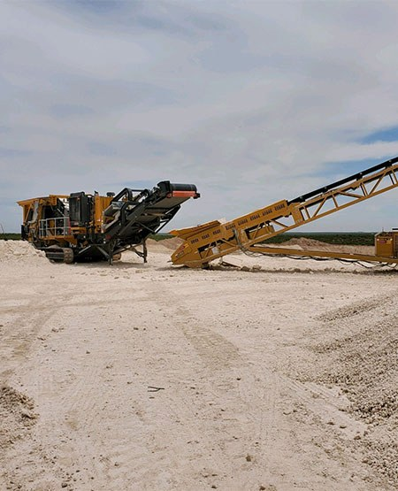Large crusher service machine from 3G construction in a large white dirt field.