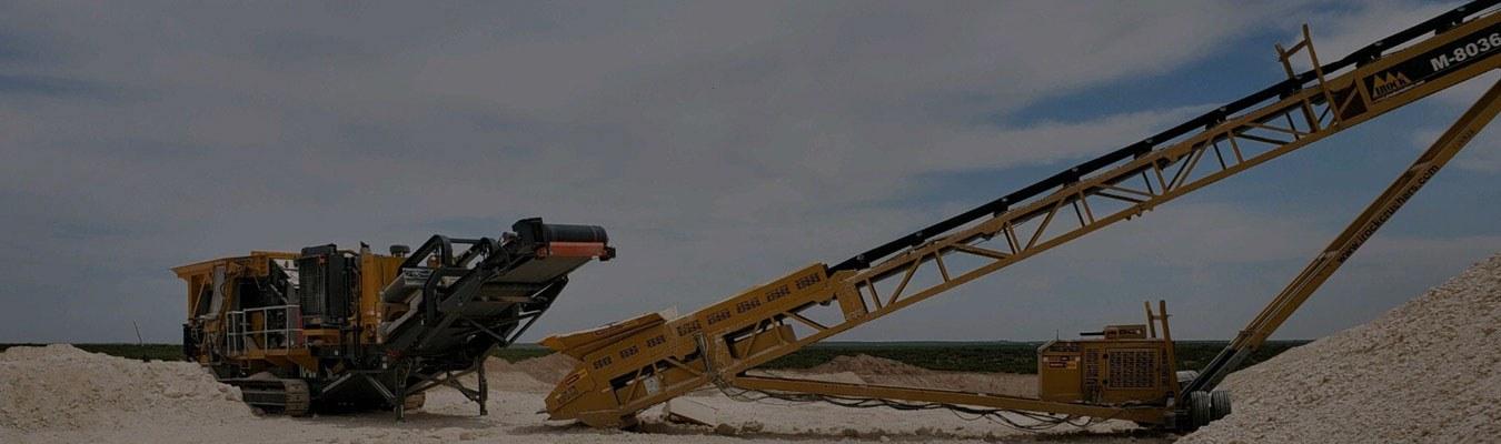 Large Crusher service equipment in a dirt field.