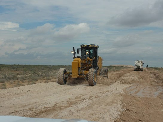 Large yellow heavy machine on a white dirt road in front of an 18 wheeler.
