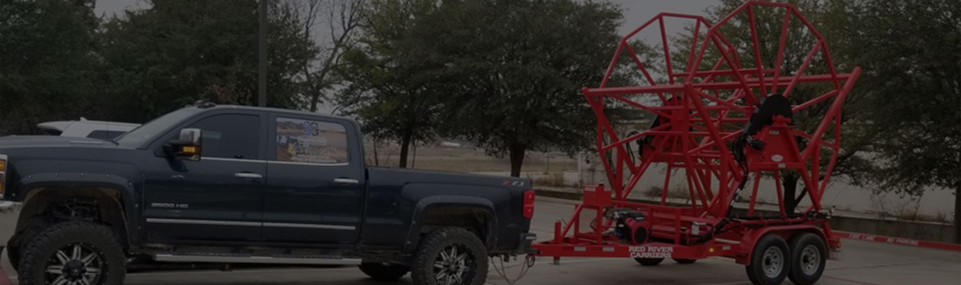 Large blue Chevy Z71 pulling red poly service equipment.