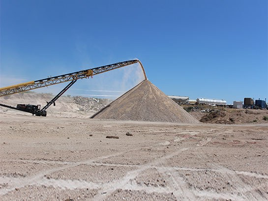 Large crusher service machine with unloading a large pile of dirt.