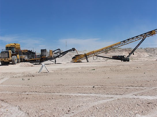 Very large crusher service equipment in a white dirt field.