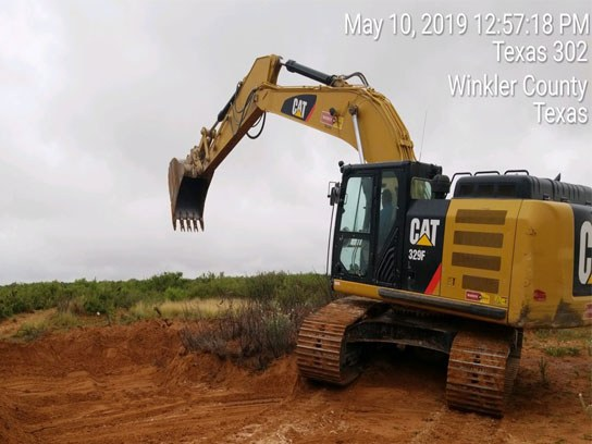Large yellow Cat branded caterpillar machine about to dig in the dirt.