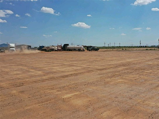 Large dirt field filled with 18 wheelers.