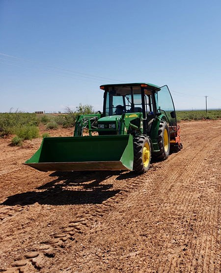 Large green tractor working in a dirt field.