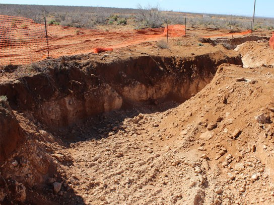 Large dirt pit with orange safety fencing around it.
