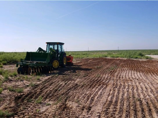 A large green tractor next to an open dirt field with clean dirt lines.