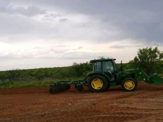 A large green tractor tilling the dirt of an open field.