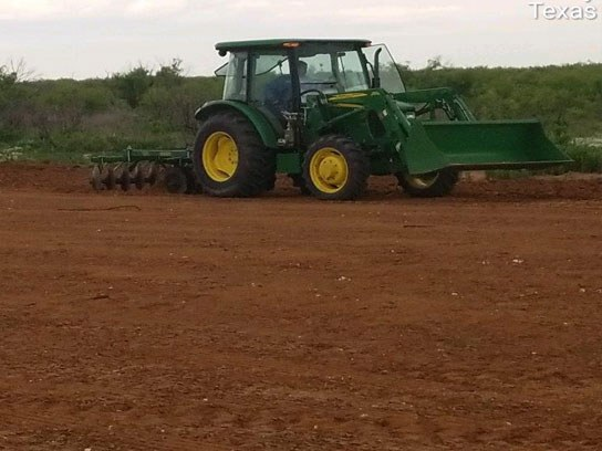 Large green tractor at work in an open dirt field.