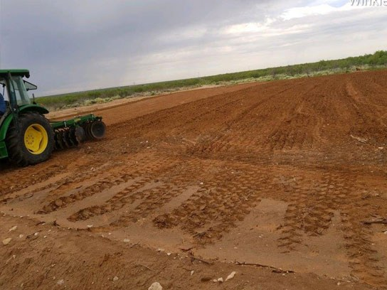 Large green tractor at work in a large open dirt field.