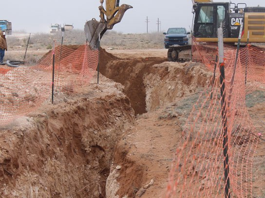 Large dirt pit with an orange safety fence surrounding it.