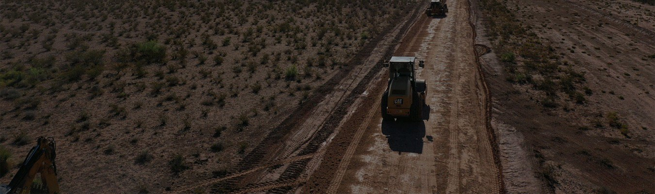 Faded background of an aerial view of heavy machinery drive down a dirt road.
