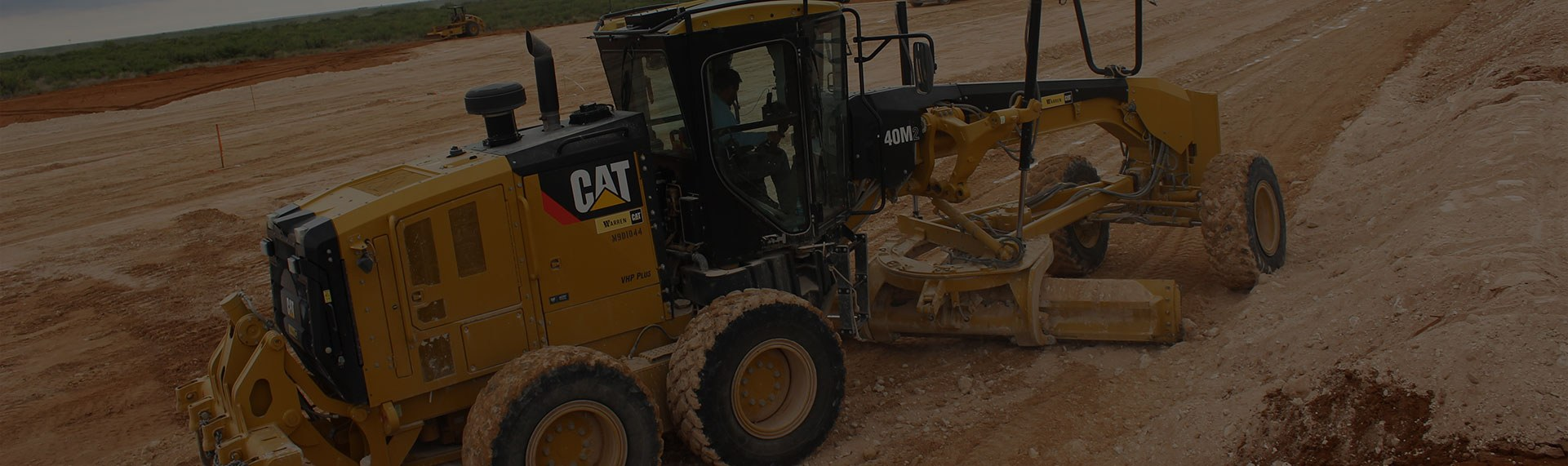 Large yellow caterpillar pulling heavy machinery in a dirt field.